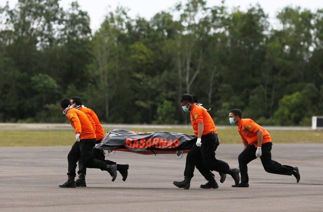 Search and rescue team members run as carry the dead body of a passenger onboard AirAsia flight QZ8501 at Iskandar airbase in Pangkalan Bun, Indonesia, December 31, 2014.  A sonar image showing a large, dark object on the sea bed is believed to be a missing AirAsia plane, an official with Indonesia's search and rescue agency said on Wednesday after bodies and debris were found in the area. Ships and planes have been scouring the Java Sea for Flight QZ8501 since Sunday, when it vanished with 162 people on board during bad weather about 40 minutes into its flight from the Indonesian city of Surabaya to Singapore. REUTERS/Beawiharta (INDONESIA - Tags: DISASTER ENVIRONMENT TRANSPORT TPX IMAGES OF THE DAY MILITARY) - RTR4JP9X